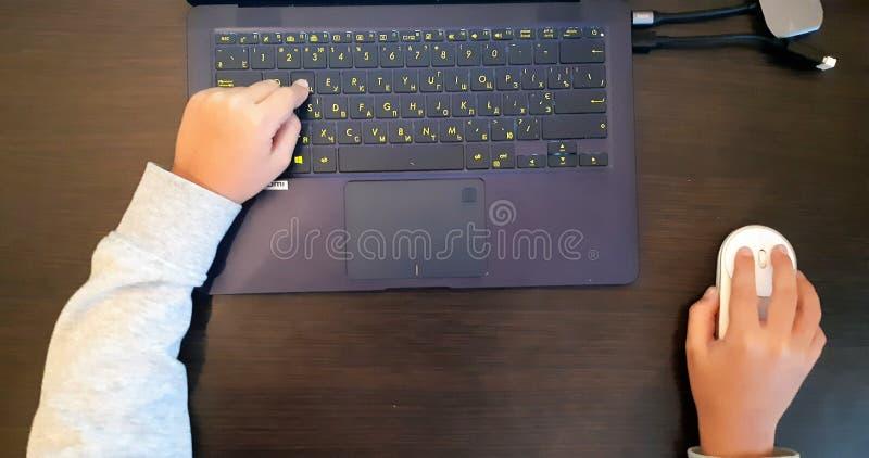 使用老鼠和键盘,关闭男小学生的手 演奏在顶视图,教育概念的手孩子计算机 免版税库存图片