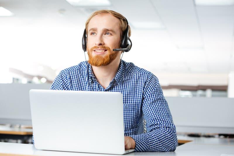 使用耳机和膝上型计算机的愉快的人在办公室 库存图片