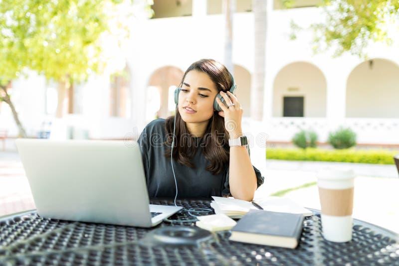 使用耳机和膝上型计算机的自由职业者在表在庭院 库存图片