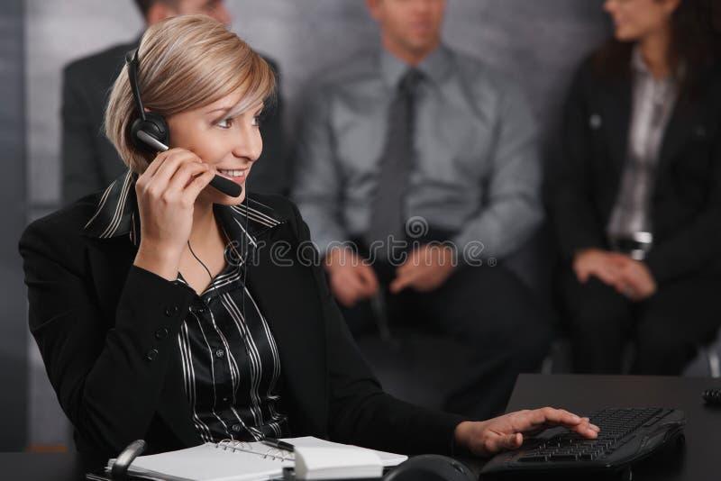 使用耳机的女实业家 免版税库存照片