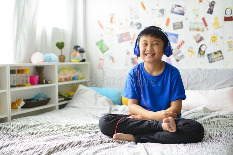 使用耳机的小亚裔男孩和微笑愉快,当在床上时的听的音乐 库存图片