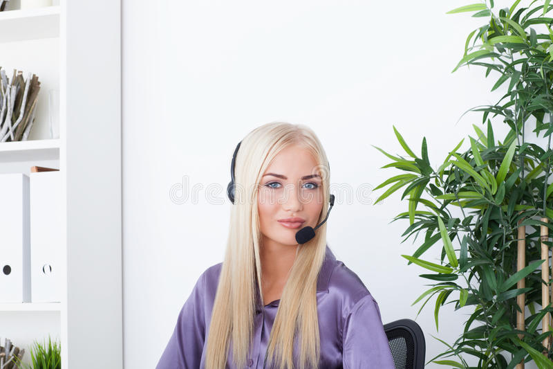 使用耳机的美丽的白肤金发,女性顾客服务操作员 免版税库存图片