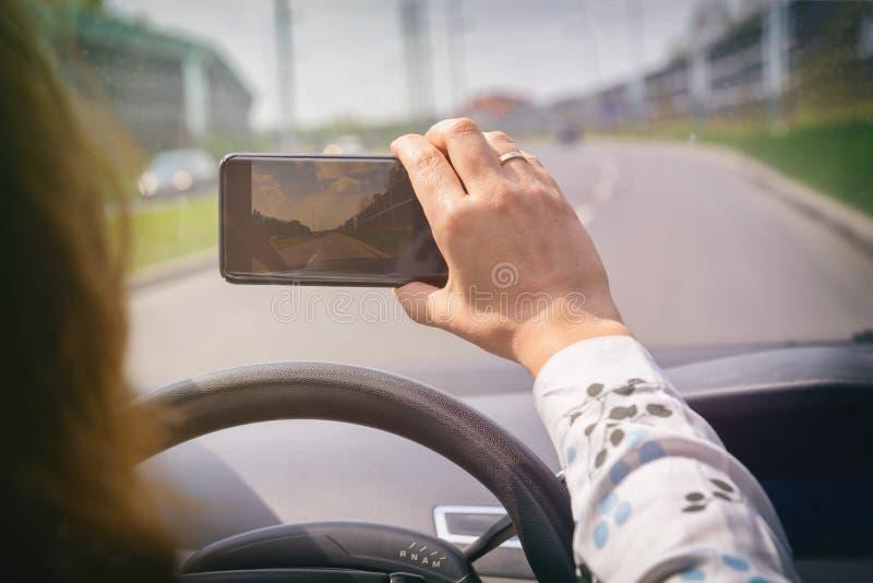 使用聪明的电话照相机的妇女,当驾驶汽车时 库存照片