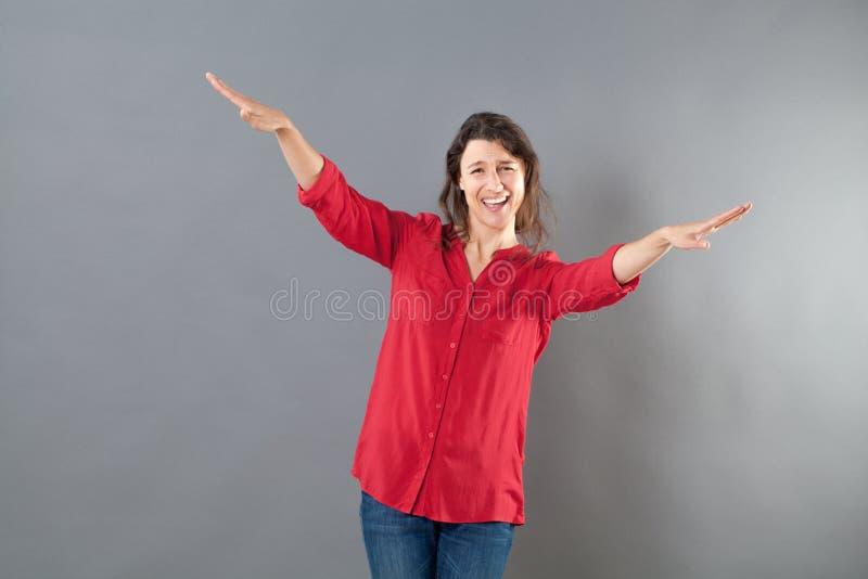 使用胳膊和手象鸟的快乐的妇女飞行 免版税库存图片