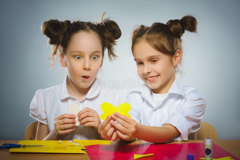 使用胶浆和剪刀,女孩做某事从色纸 免版税库存图片