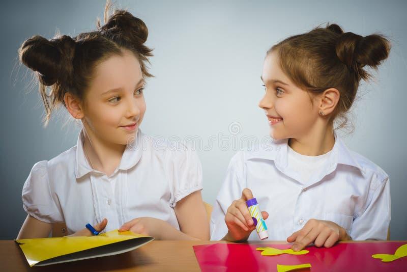 使用胶浆和剪刀,女孩做某事从色纸 免版税库存照片