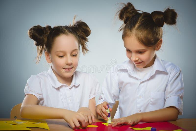 使用胶浆和剪刀,女孩做某事从色纸 免版税图库摄影