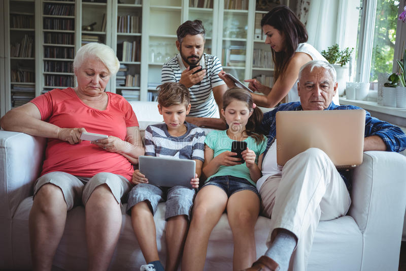 使用膝上型计算机、手机和数字式片剂的多代的家庭 免版税图库摄影
