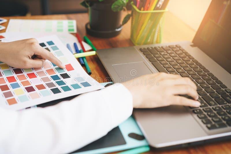 使用膝上型计算机剪影布局设计的艺术家创造性的设计师手 免版税库存照片