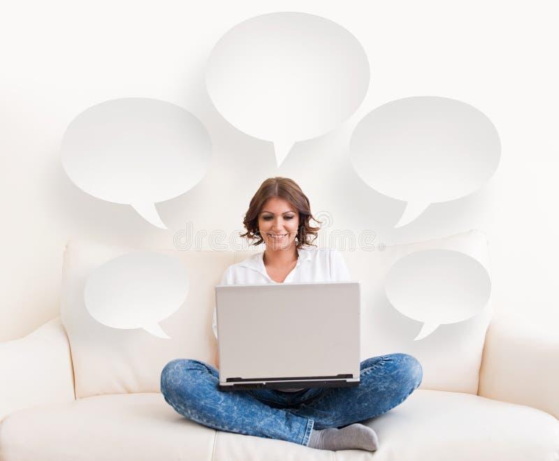 使用膝上型计算机和一个电话在沙发的妇女 库存图片