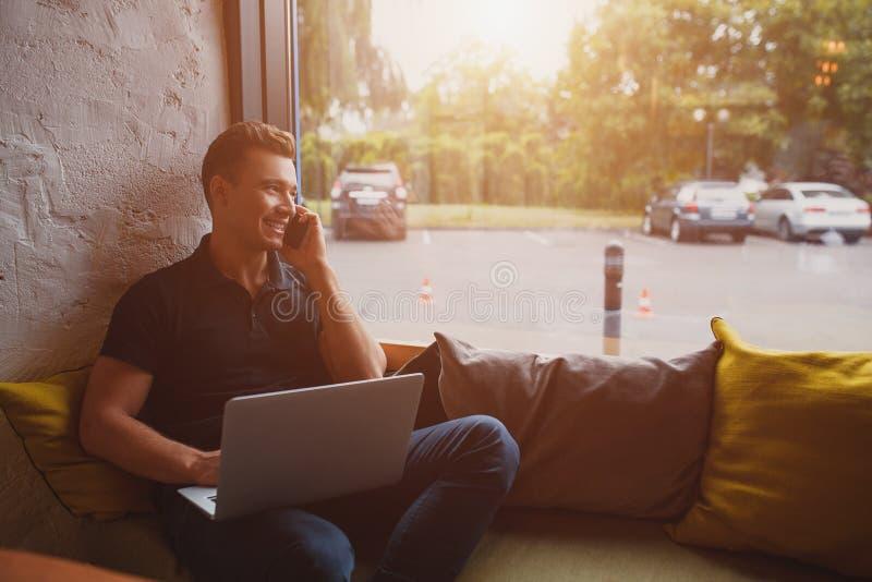 使用膝上型计算机和手机在长沙发的愉快的年轻人 免版税库存照片