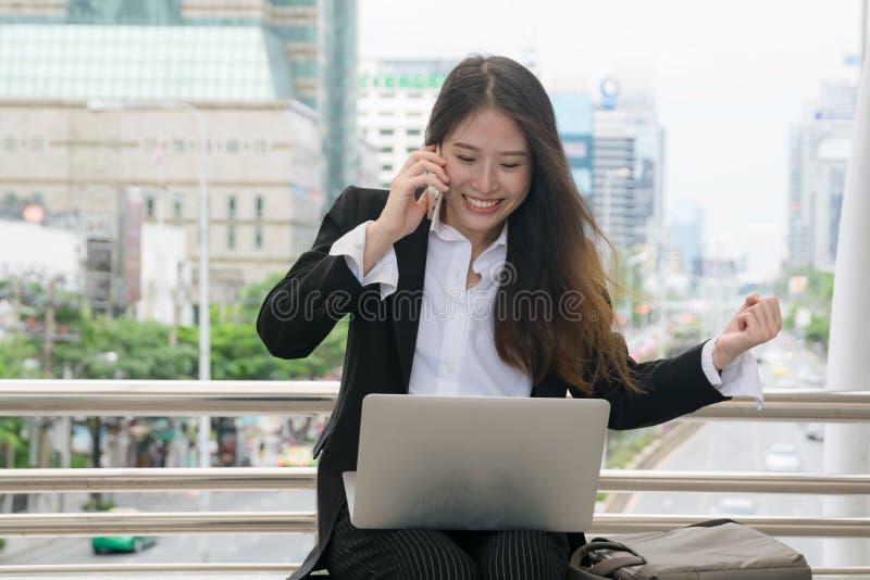 使用膝上型计算机和手机的亚裔女商人有愉快的面孔的,概念成功工作 库存照片