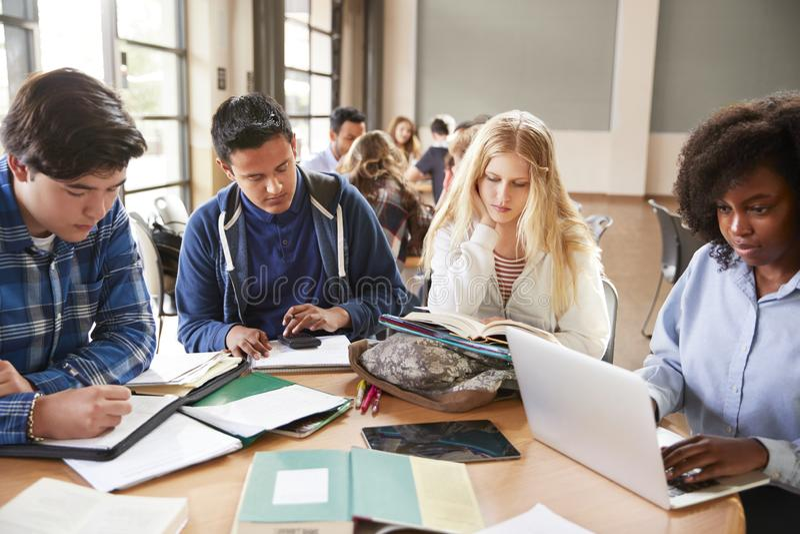 使用膝上型计算机和数字式片剂的高中学生运转与女老师在书桌 免版税库存图片