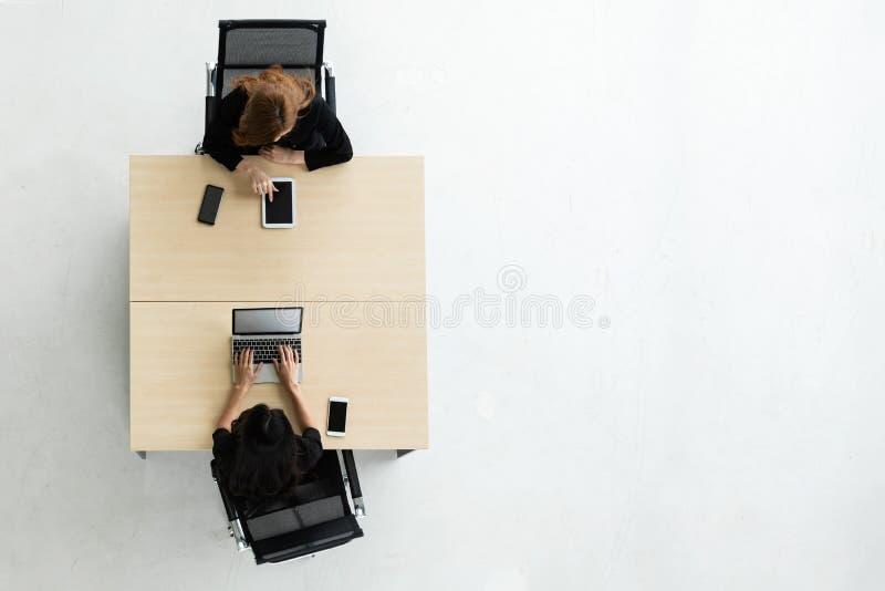使用膝上型计算机和数字片剂的亚裔女实业家顶视图  免版税库存图片
