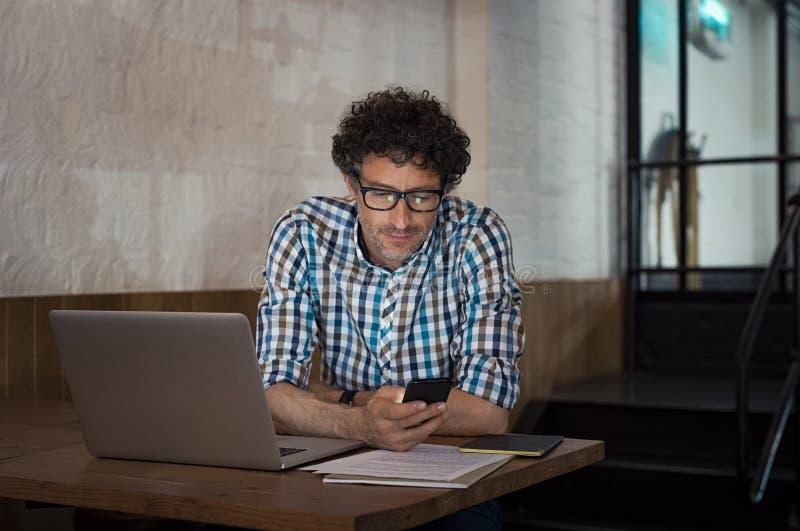 使用膝上型计算机和智能手机的人在咖啡馆 库存照片