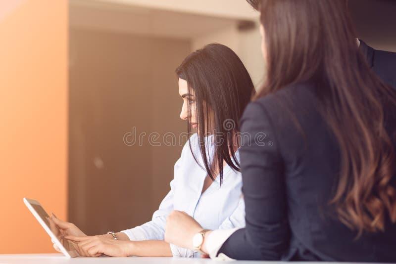 使用膝上型计算机和片剂计算机,起始的企业年轻创造性的人民在办公室编组在会议的激发灵感 免版税图库摄影