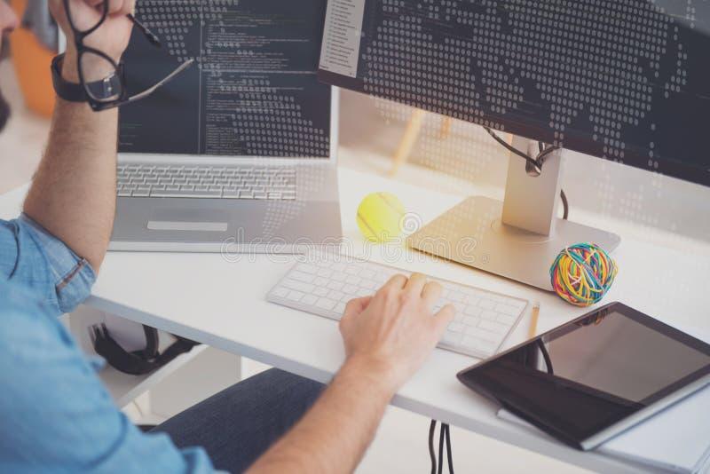 使用膝上型计算机和计算机的勤勉人在办公室 图库摄影
