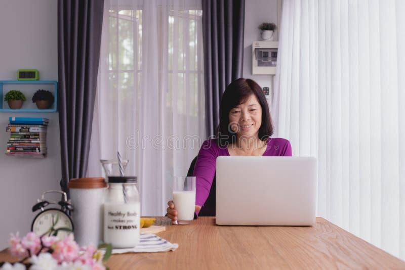 使用膝上型计算机和饮用奶的亚裔老人在家 免版税库存照片