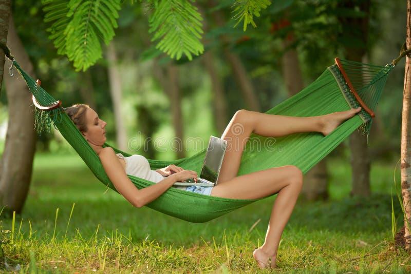 使用膝上型计算机在热带公园 图库摄影