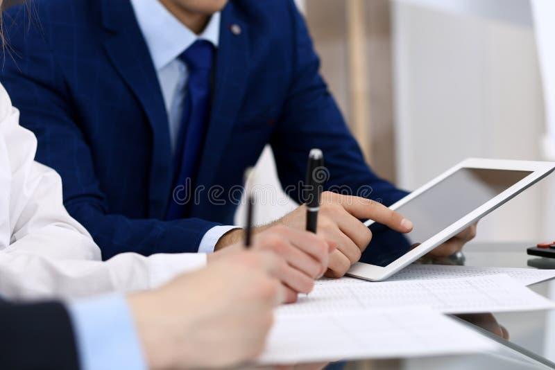 使用膝上型计算机在见面,手特写镜头的商人  经营活动概念 免版税库存图片