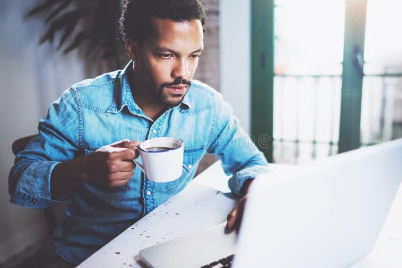 使用膝上型计算机家的沉思有胡子的非洲人,当水杯无奶咖啡在木桌时 年轻人的概念 免版税库存图片