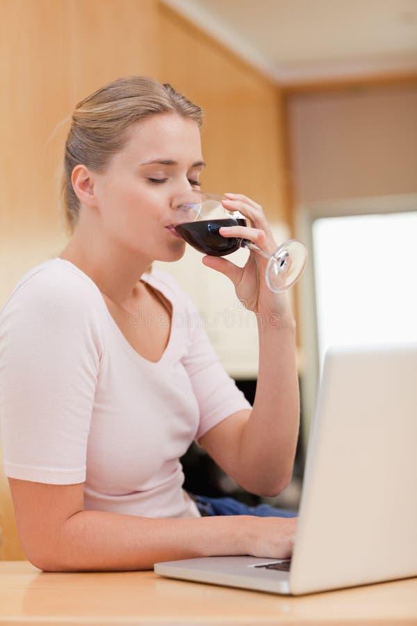 使用膝上型计算机的一个少妇的纵向,当喝红葡萄酒时 免版税图库摄影