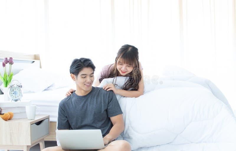 使用膝上型计算机的一对夫妇在他们的卧室 库存照片