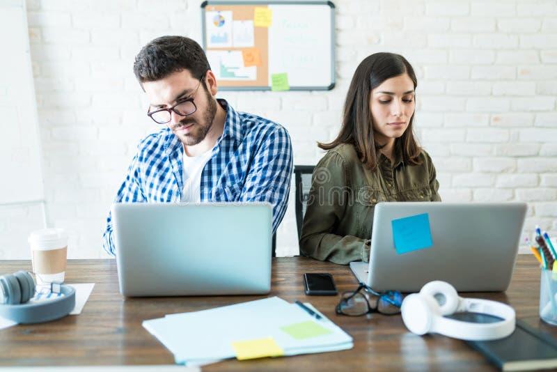 使用膝上型计算机的专家在工作场所 免版税库存照片