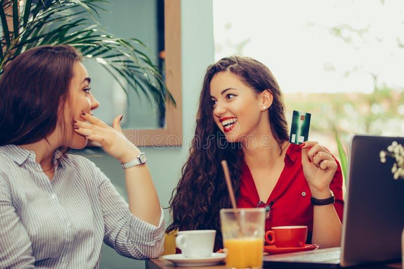 使用膝上型计算机的两美女为在网上购物与信用卡支付 免版税库存图片