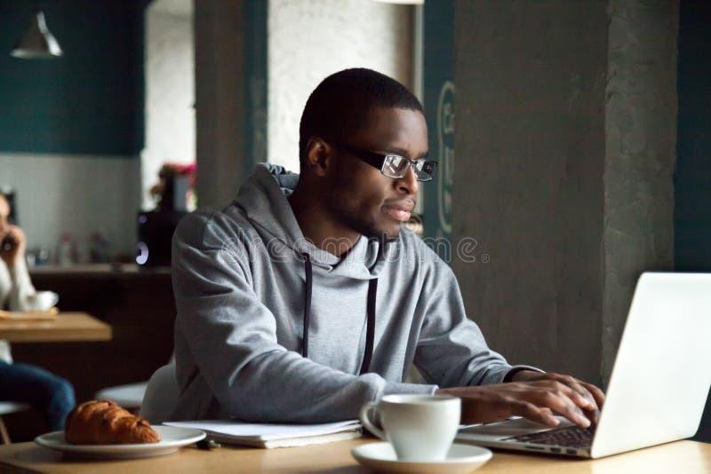 使用膝上型计算机的严肃的千福年的非裔美国人的人坐在 库存照片