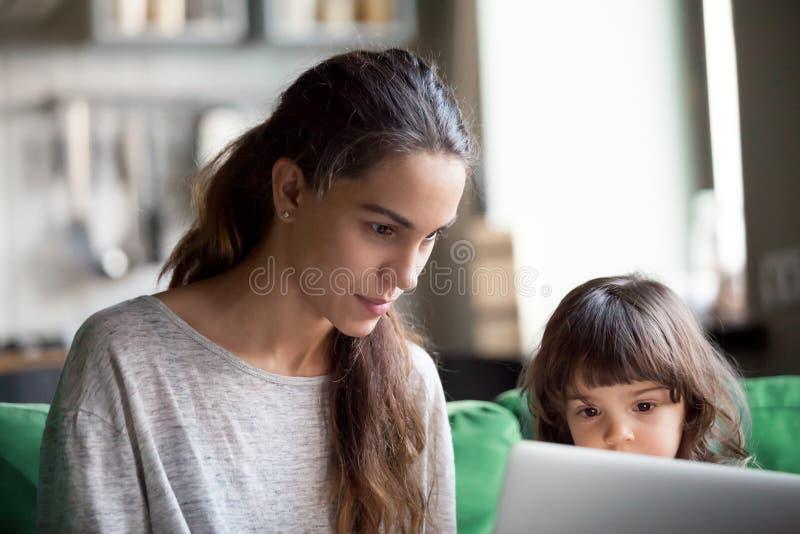 使用膝上型计算机的严肃的单亲母亲与女儿一起 免版税库存照片