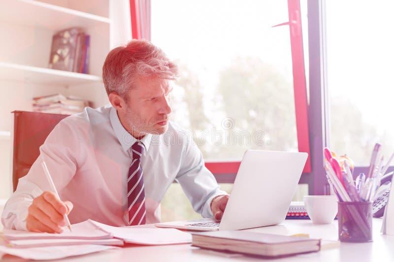 使用膝上型计算机的严肃的商人,当做文书工作在书桌在办公室时 免版税库存照片