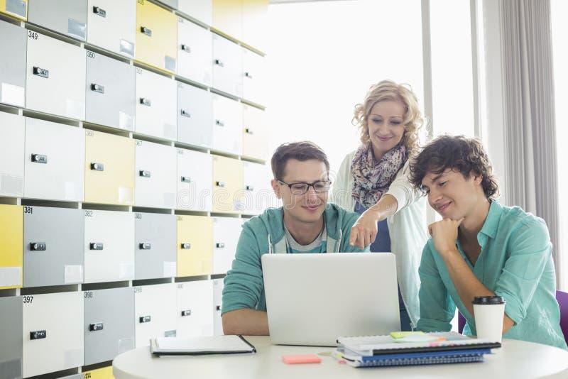 使用膝上型计算机的买卖人在桌在更衣室在创造性的办公室 免版税库存图片