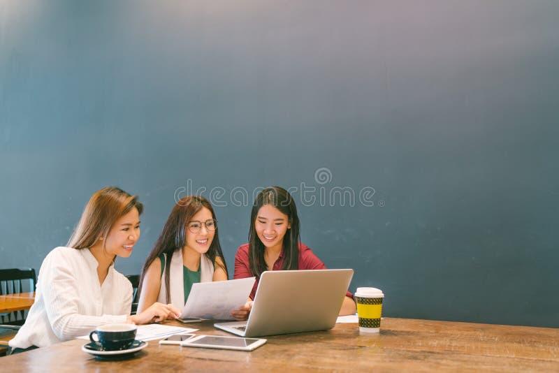 使用膝上型计算机的亚裔女孩在队业务会议、工友或者大学生、起始的项目讨论或者配合突发的灵感 免版税库存照片