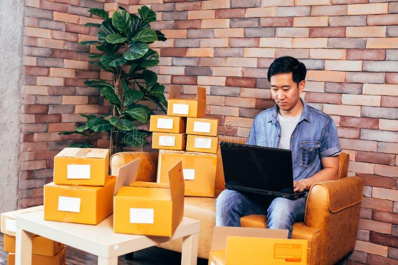 使用膝上型计算机的亚裔男性企业家有盒的箱子在家 库存照片