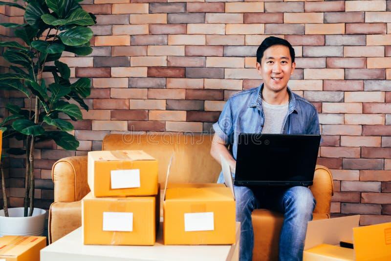 使用膝上型计算机的亚裔男性企业家有盒的箱子在家 免版税库存照片
