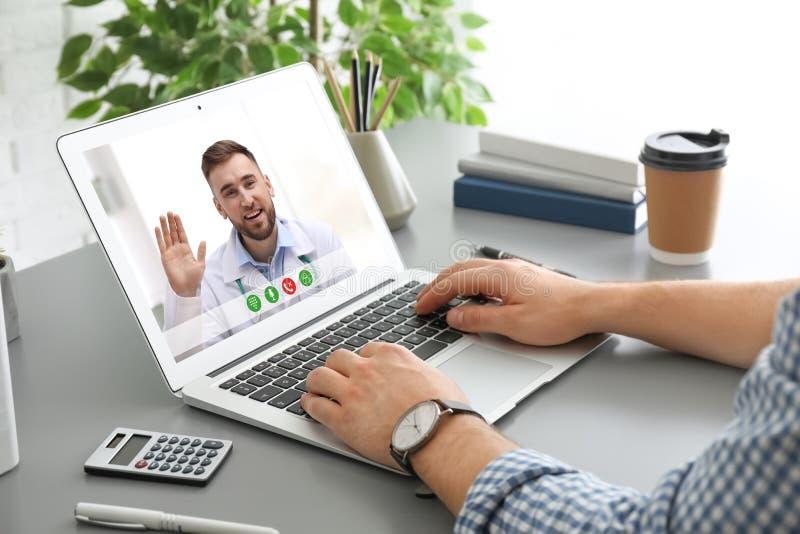 使用膝上型计算机的人与医生的网上咨询的通过视频聊天在桌上 免版税库存图片