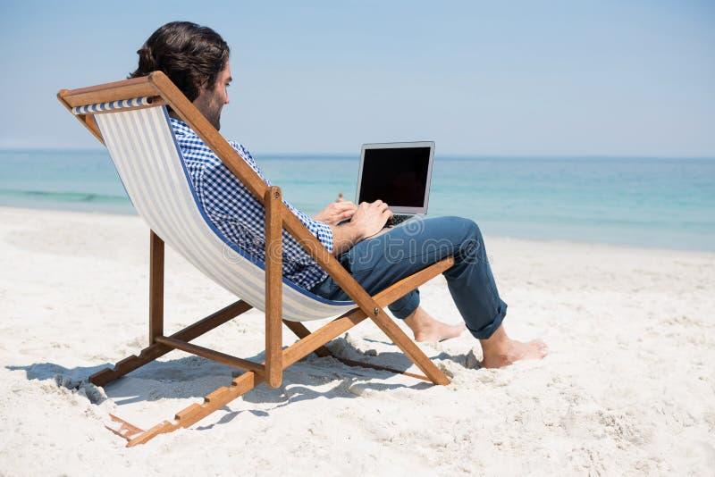 使用膝上型计算机的人侧视图在海滩 免版税图库摄影