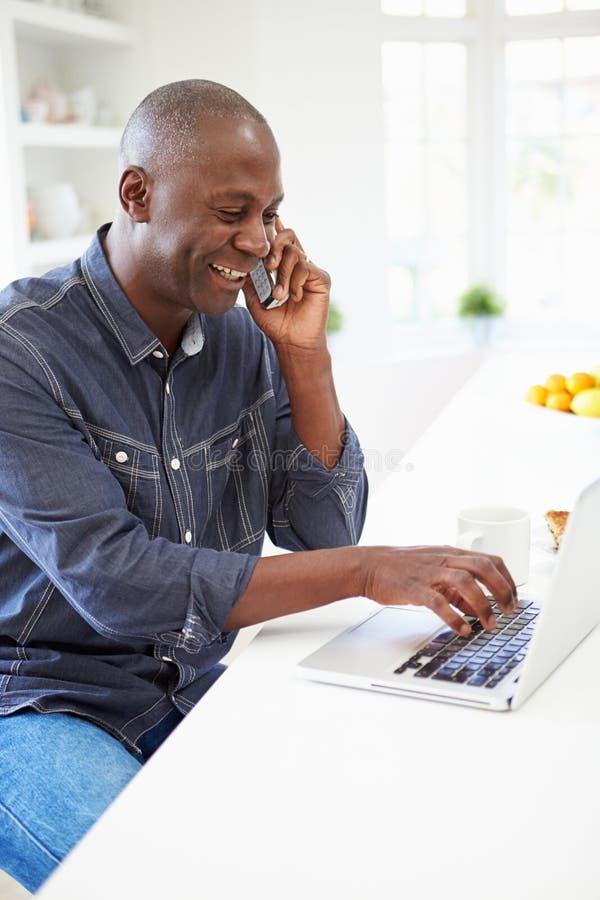 使用膝上型计算机的人和在家谈话在电话在厨房 免版税库存图片