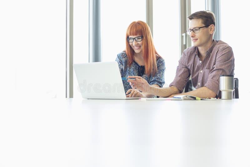 使用膝上型计算机的企业同事在书桌在创造性的办公室 免版税库存照片