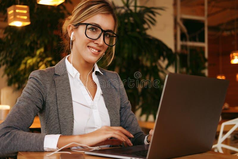 使用膝上型计算机的企业wooman在咖啡馆 坐在咖啡馆和研究计算机的年轻美女 免版税库存照片