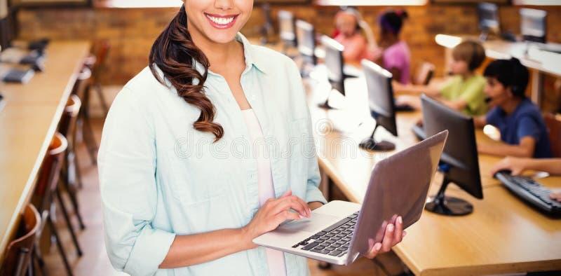 使用膝上型计算机的俏丽的老师画象在计算机类 库存图片