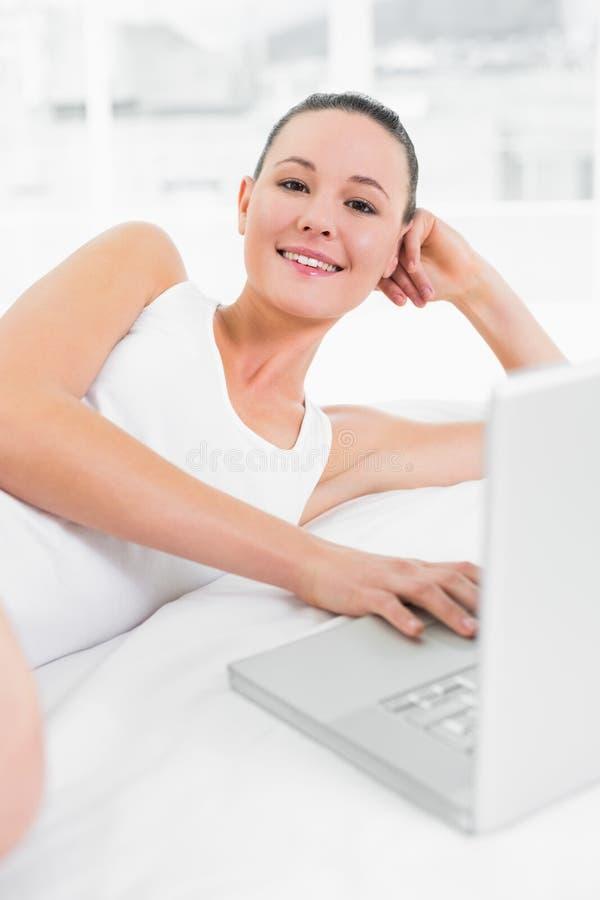 使用膝上型计算机的偶然微笑的妇女在床 免版税库存图片