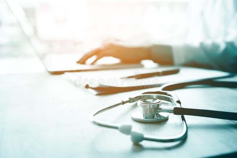 使用膝上型计算机的医生在书桌在研究计算机的诊所在roo 免版税库存图片