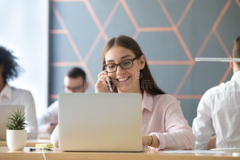 使用膝上型计算机的千福年的微笑的女实业家谈话在电话a 免版税库存照片