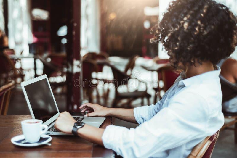 使用膝上型计算机的卷曲人自由职业者在咖啡馆 免版税库存图片