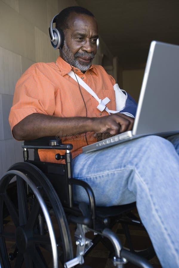 使用膝上型计算机的受伤的人和听到音乐 免版税库存照片