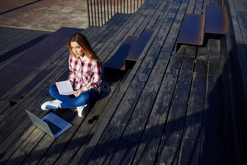 使用膝上型计算机的可爱的少妇坐享受晴天的木楼梯户外 免版税库存照片