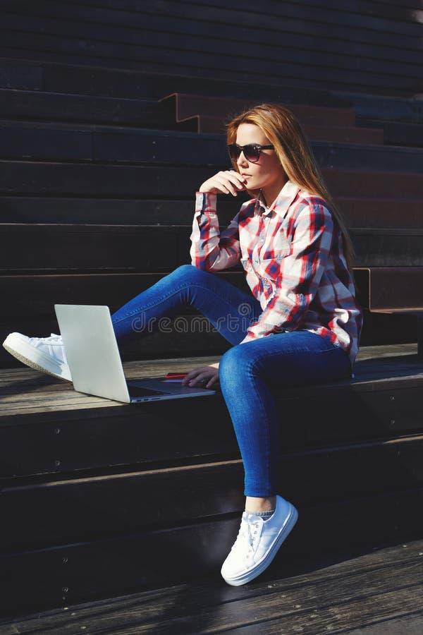 使用膝上型计算机的可爱的少妇坐享受晴天的木楼梯户外 库存照片