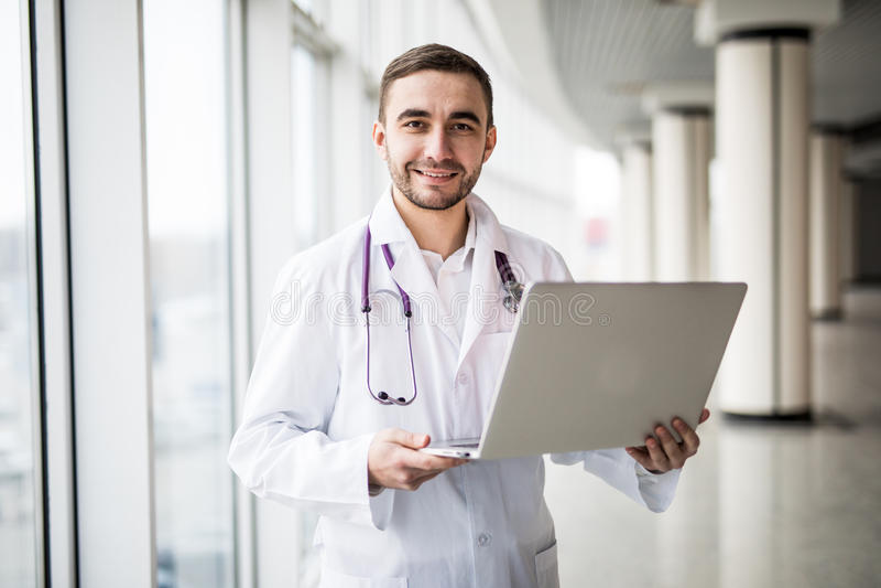 使用膝上型计算机的可爱的年轻医护人员 免版税图库摄影